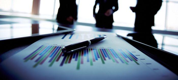 Gráfico sobre a mesa com caneta com pessoas ao fundo