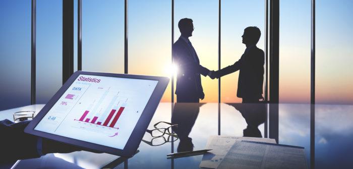 tablet com gráfico de estatísticas e silhueta ao fundo de 2 homens apertado as mão