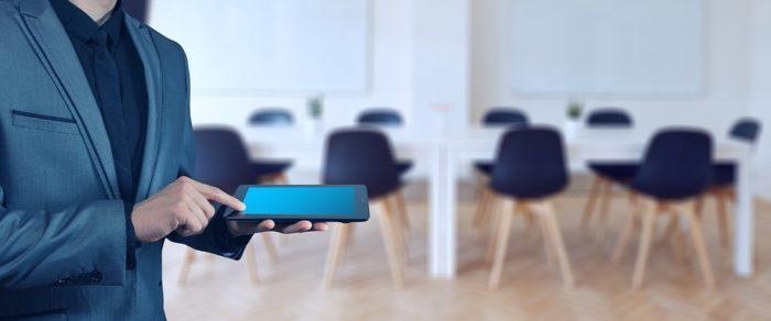 homem com smartphone na mão em um sala com cadeiras ao fundo