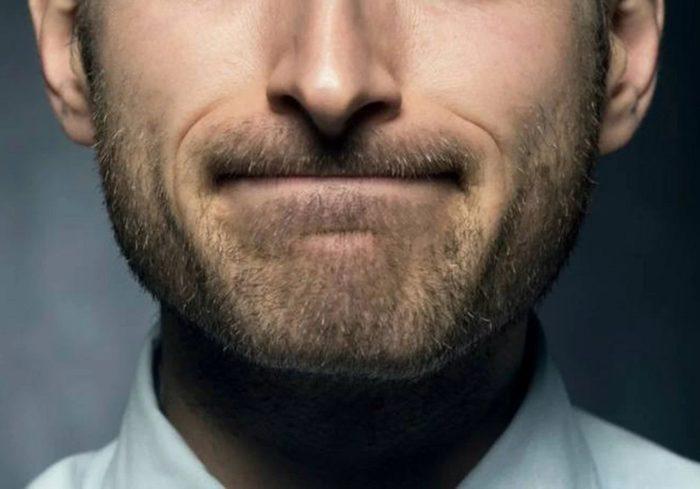 homem comprimindo os lábios
