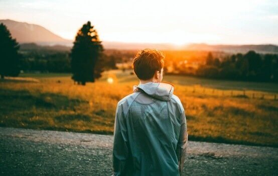 homem olhando para o horizonte ao por do sol