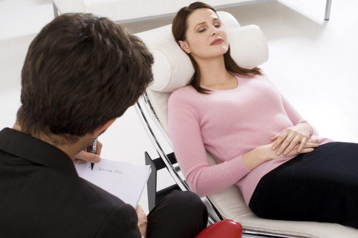 mulher deitada no divã fazendo hipnose